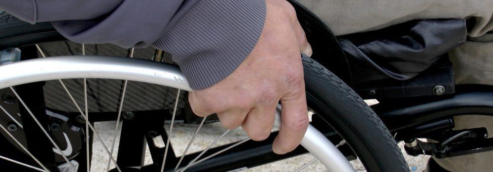 Hand holding wheelchair wheel